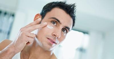 Man som smörjer i ögonpartiet med vårdande ögonkräm.