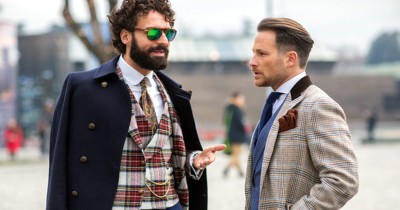 Två stiliga herrar diskuterar sina skägg.