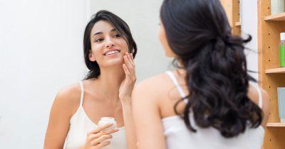 Unga kvinna applicerar hudvård