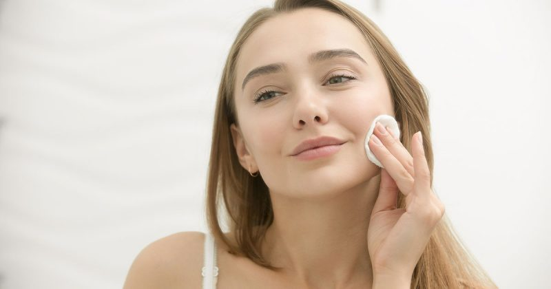 Unga kvinna, pigmentfläckar, tvätta ansiktet