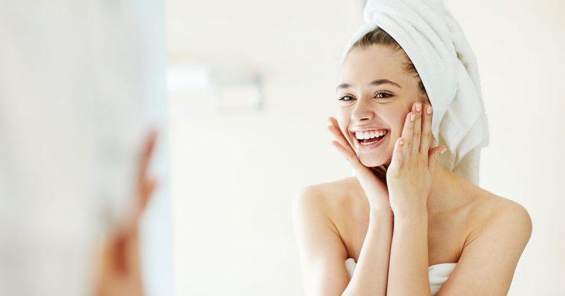 Ung kvinna, hudvårdsrutin, tvättar ansiktet