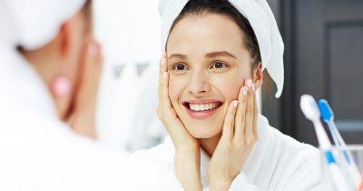 Ung kvinna, tittar i spegel, händerna på ansiktet, tvättar ansiktet