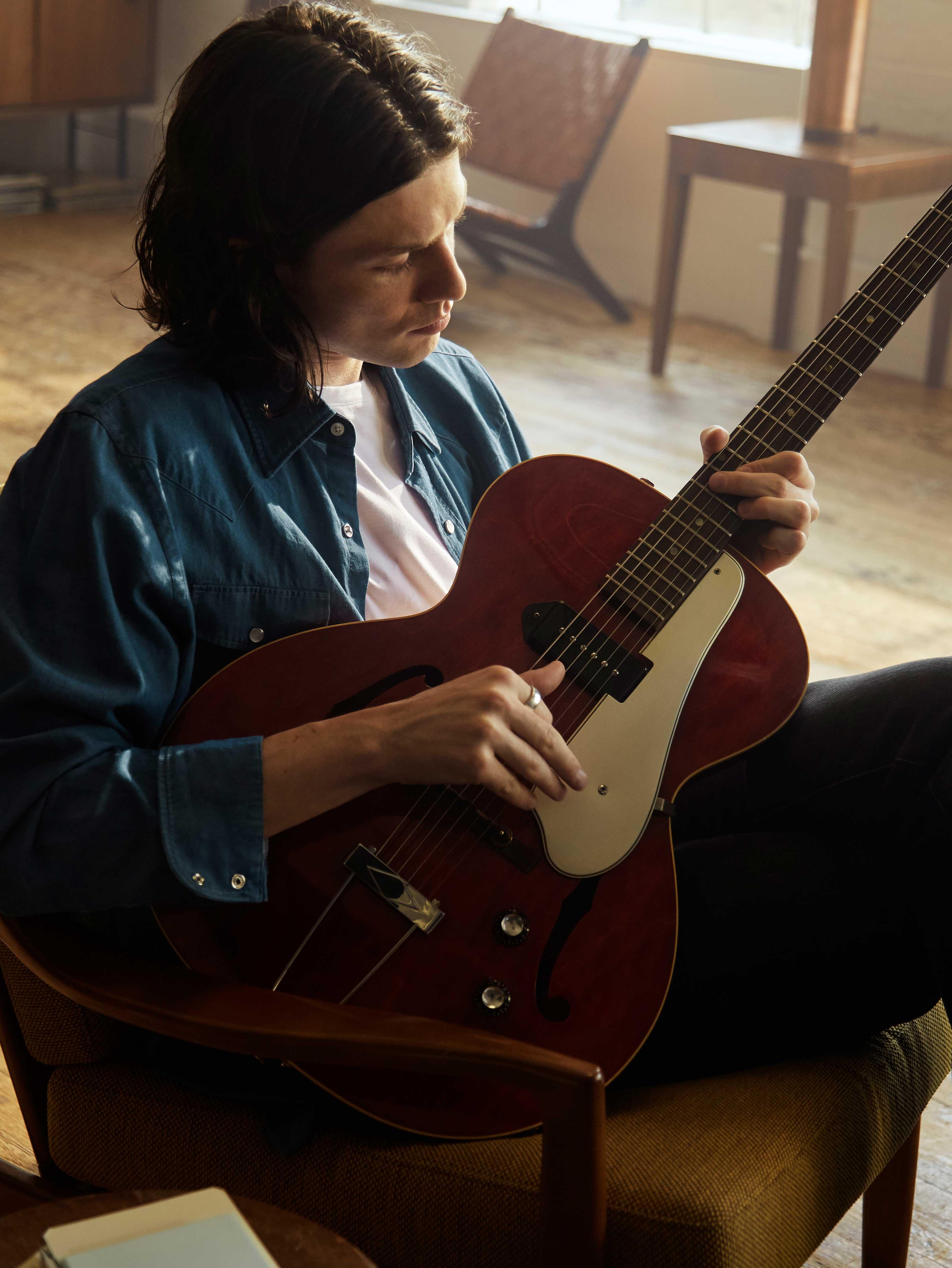James Bay sitter på en stol och spelar gitarr